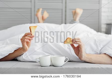 Cheerful man and woman are enjoying breakfast together. They are lying under blanket on bed near cups and holding toasts