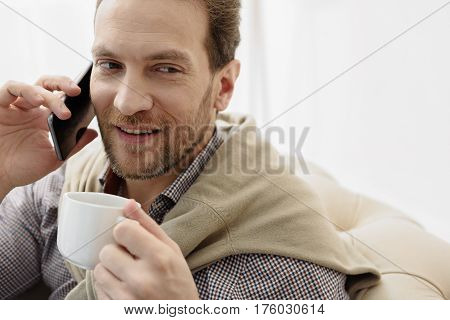 Confident man is talking on mobile phone while drinking coffee. He is sitting on couch and laughing