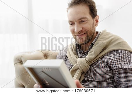 I miss my family. Cheerful man is looking at photo frame and smiling. He is sitting on couch with relaxation