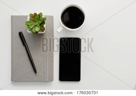 Top view close up of cup of coffee, smartphone, pen and plant on notebook on white table. Copy space in right side
