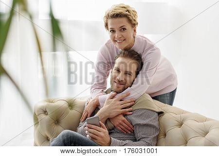 Happy married couple is enjoying time together. Man is sitting on sofa and holding phone. Woman is standing and embracing him with love