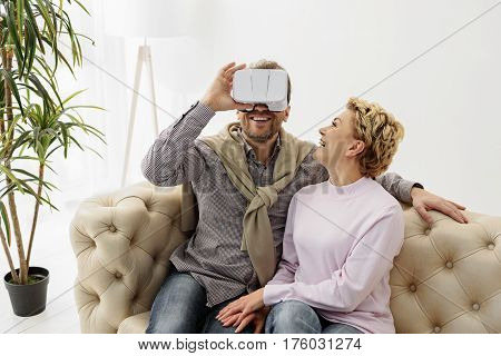 Joyful married couple entertaining with modern technology at home. Man is watching vr device with excitement. Woman is sitting near him on couch and laughing