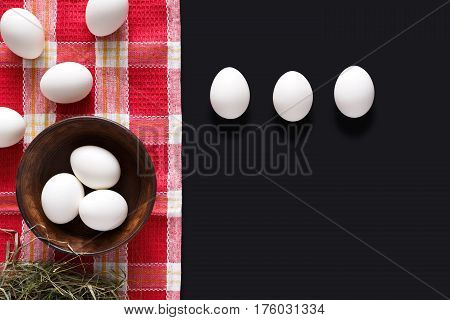 Easter mockup. White eggs unpainted, pattern for your colors, in bowl on napkin at black background decorated with pussy willow spring flowers. Top view with copy space