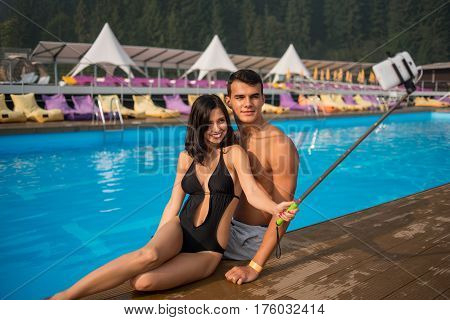 Portrait Of Romantic Couple Sitting On The Edge Of Swimming Pool At The Luxurious Resort And Taking