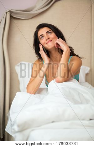 Lady in bed with phone. Woman holding smartphone and smiling. Good morning, darling.