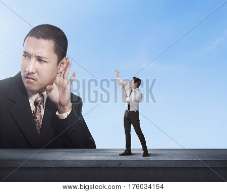 Attractive business man using megaphone to scream at boss man with blue sky background