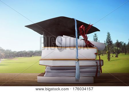 Mortarboard And Graduation Scroll With Stack Of Book
