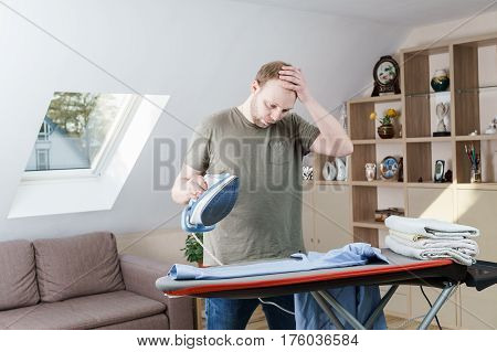 Handsome young man ironing shirt at home