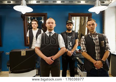 Young professional barbers team posing to camera inside modern barbershop. Four masculine male hairstylists standing indoors at workplace in hair salon