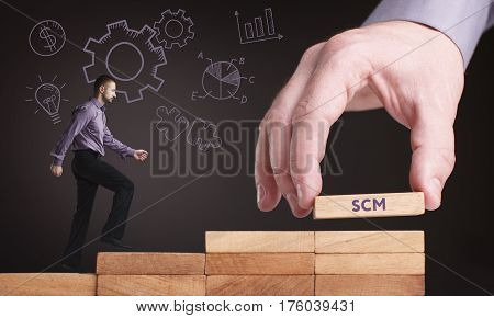 Business, Technology, Internet And Network Concept. Young Businessman Shows The Word: Scm