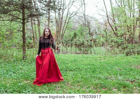 mystical witch woman in a red skirt with a candle in spring forest
