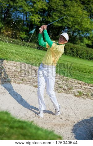 Man playing golf  from bunker during summer time