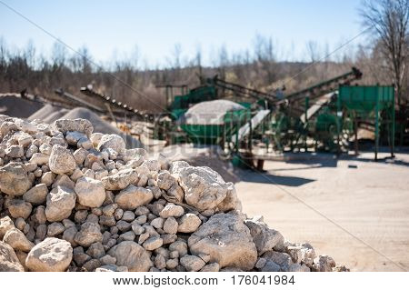 Pile Of Gravel-rock.blurred On Background Machinery Of Quarry.