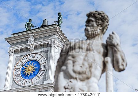 Clock tower with bell. Blurred in foreground the Hercules Statue.