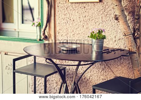 Vase With Primroses In Bloom On A Table Outside.