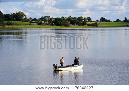 BLITHBURY, UNITED KINGDOM - OCTOBER 2, 2016 - Two fishermen in a small boat on Blithfield reservoir Blithbury Staffordshire England UK, October 2, 2016.