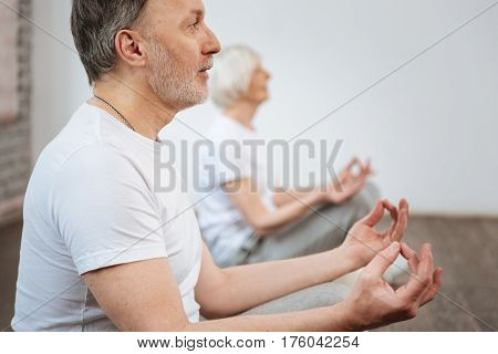 Keep calm. Delighted bearded man wearing white T-shirt putting his thumb and middle finger together sitting next to his wife