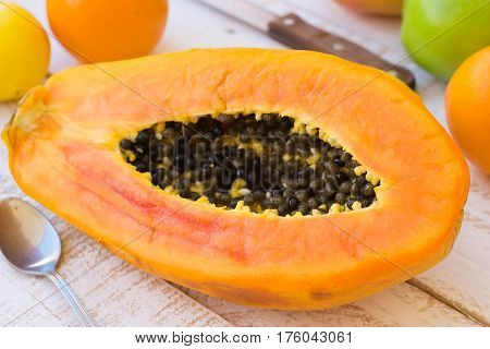 Ripe juicy halved papaya on kitchen table with citrus fruits and apples knife on plank wood table outdoors top view