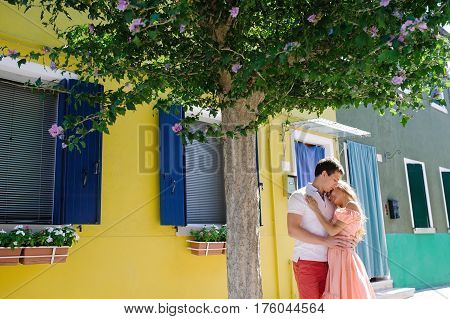 Young romantic couple embracing under a tree Burano Venice Italy Europe