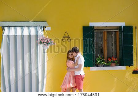 Happy couple embracing near a yellow house in Burano island Venice Italy Europe