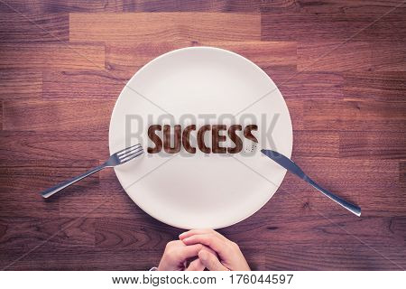 Leadership is hungry for success. Motivational concept. Businessman with plate and cookies with text success.