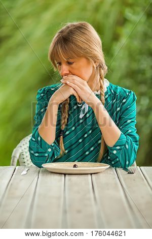Young woman is having meager meal in times of scarcity.