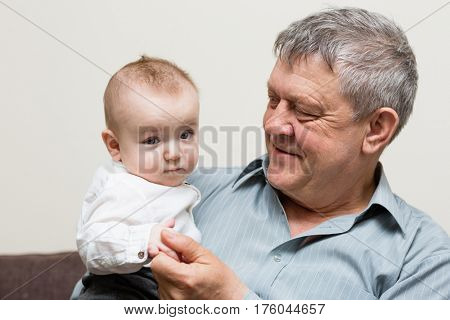 Close-up portrait of grandfather and grandson. The child is six months old. The child is six months old.