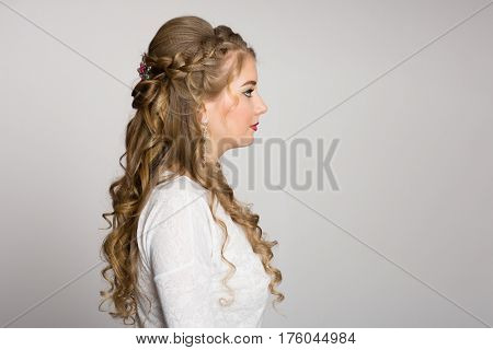 Portrait of a girl with a fashionable hairstyle with curls in profile