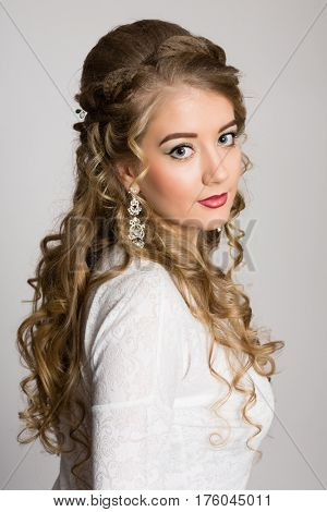 Portrait of a girl with long fashionable hair on a gray