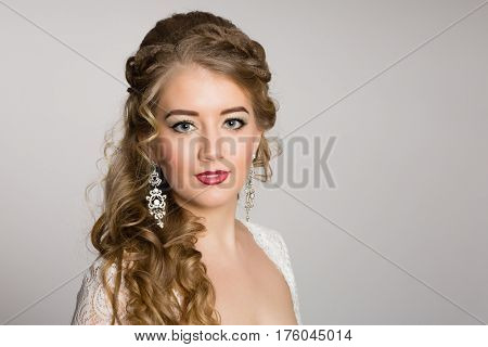 Portrait of a girl with a bride's hair on a gray