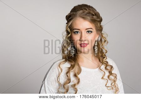Portrait of a pretty girl with a fashionable hairstyle with curls on a gray background