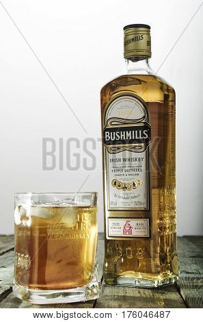 Bushmills Whiskey Glass And Bottle On Green Wooden Table
