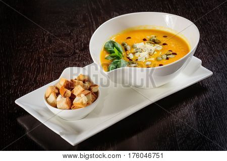 Roasted pumpkin soup with cream and pumpkin seeds on dark wooden background. Copy space.