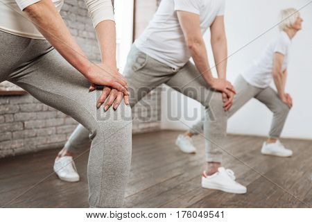 Try to repeat. Close up of hands touching knee that wearing grey trousers