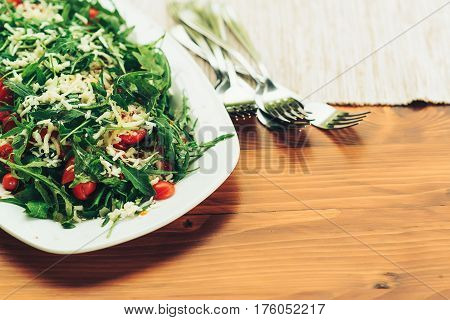 Fresh salad with tomato, ruccola on the kitchen table.