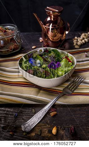 Colorfull Salad with Edible Flowers on a dark table