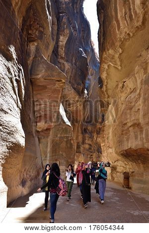 PETRA JORDAN - APR 2 2015: Tourists walking in Siq canyon in Petra. Petra's temples tombs theaters and other buildings are scattered over 400 square miles. UNESCO world heritage site and one of The New 7 Wonders of the World