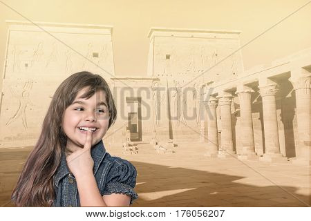 Smiling long haired tanned little girl with her finger over her mouth is standing in front of Philae temple in Egypt. Landmark in the background is edited as a vintage photo in sunlight.