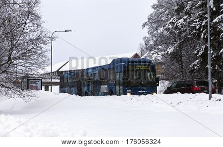 UMEA, SWEDEN ON MARCH 02. View of a bus by a bus stop along a snowy road on March 02, 2017 in Umea, Sweden. Buildings, houses in the background. Editorial use.