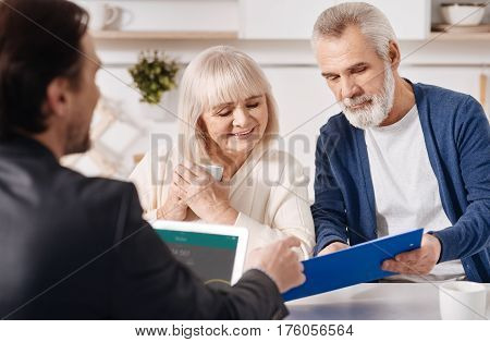Discussing all details. Attentive cheerful concentrated old couple sitting at home and concluding agreement with real estate advisor while reading the contract attentively
