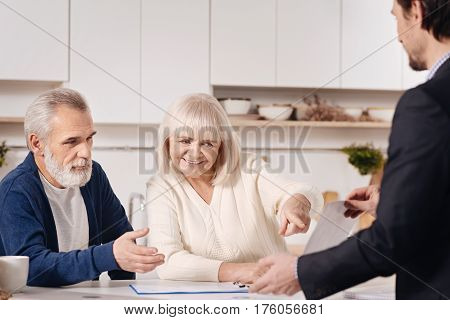 Sharing opinions. Happy pleasant old couple sitting at home and discussing agreement with real estate agent while exchanging opinions