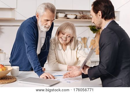 Doing my job properly . Skillful optimistic sincere real estate agent having conversation with elderly customers and using important documents while representing the house