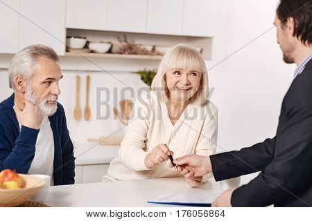 Full of determination. Experienced proficient skilled social security advisor having conversation with aged clients and working while preparing documents for signing