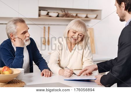 The moment of signing the agreement. Decisive positive senior couple sitting at home and having conversation with social security advisor while signing the agreement