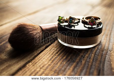 a powder and brush with jewels on wooden background