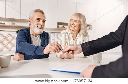 Thinking about our future. Smiling satisfied aged couple sitting at home and having conversation with finance advisor while signing the agreement