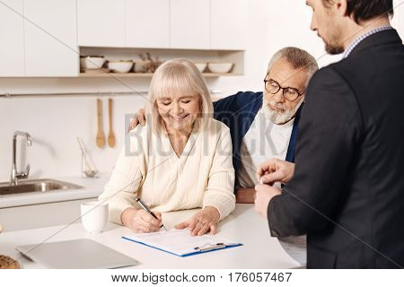 Signing our deal. Smiling charming positive elderly woman sitting at home next to her husband and having meeting with broker while signing documents
