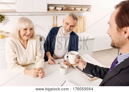 Enjoyable working hours. Amused glad cheerful notary having meeting and enjoying the hospitality of aged couple of clients while expressing holding the cup of tea