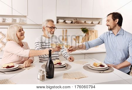 Enjoyable family evening. Delighted happy cheerful pensioners having dinner and enjoying day with their mature son while raising glasses full of champagne