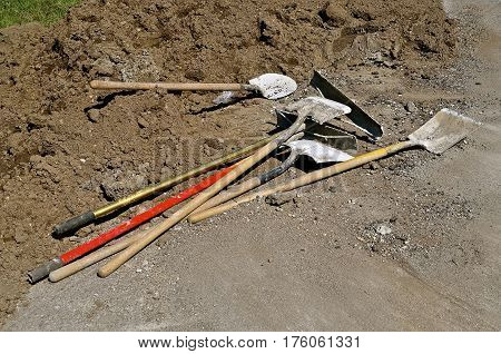 Various kids of shovels are available for usage in the repair and construction of a curb and street repair project.
